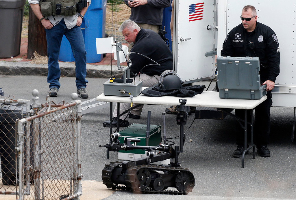 Description of . A member of the Cambridge police bomb squad, right, deploys a robot on Norfolk Street during a search for searching a suspect in the Boston Marathon bombings in Cambridge, Mass., Friday, April 19, 2013.(AP Photo/Michael Dwyer)