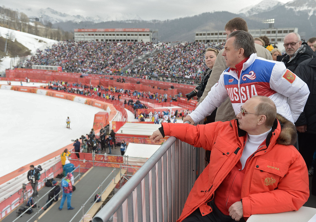 Description of . Russian President Vladimir Putin (foreground) watches a men's Alpine skiing event at the Rosa Khutor centre at the Sochi 2014 Winter Paralympics on March 9, 2014.  ALEXEY NIKOLSKY/AFP/Getty Images