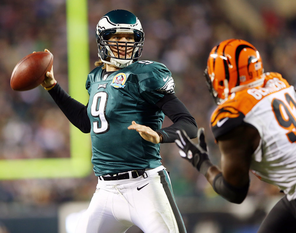 Description of . Nick Foles #9 of the Philadelphia Eagles passes under pressure from Robert Geathers #91 of the Cincinnati Bengals on December 13, 2012 at Lincoln Financial Field in Philadelphia, Pennsylvania.  (Photo by Elsa/Getty Images)