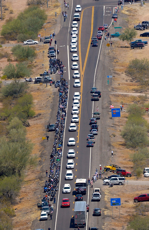 Description of . A procession of 19 hearses for the 19 fallen Arizona firefighters drives through the desert, Sunday, July 7, 2013, near Wickenburg, Ariz, The elite crew of firefighters were overtaken by the out-of-control blaze as they tried to protect themselves from the flames under fire-resistant shields last Sunday.  (AP Photo/Mark J. Terrill)