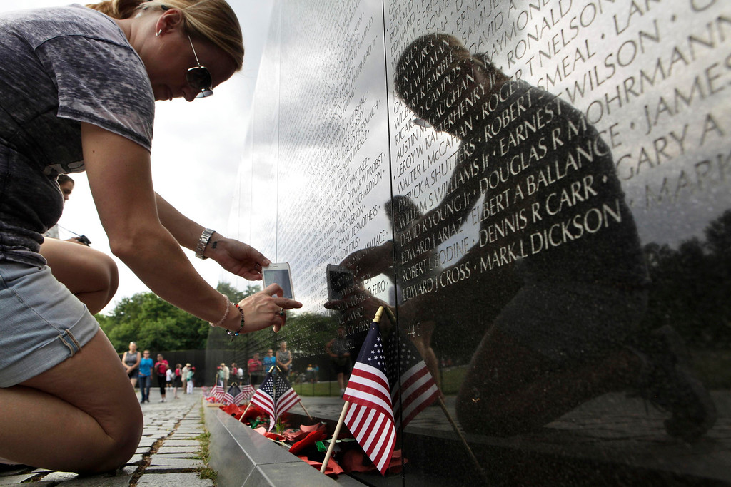 Description of . A woman takes pictures of the Vietnam Veterans Memorial wall, etched with the names of more than 58,000 U.S. servicemen and women who died in the war, in Washington May 23, 2013. Memorial Day falls on May 27 this year.   REUTERS/Yuri Gripas