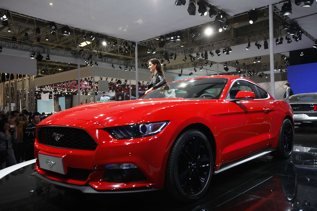 Description of . A model poses by a red Mustang 50th anniversary edition car on display at the China International Exhibition Center new venue during the