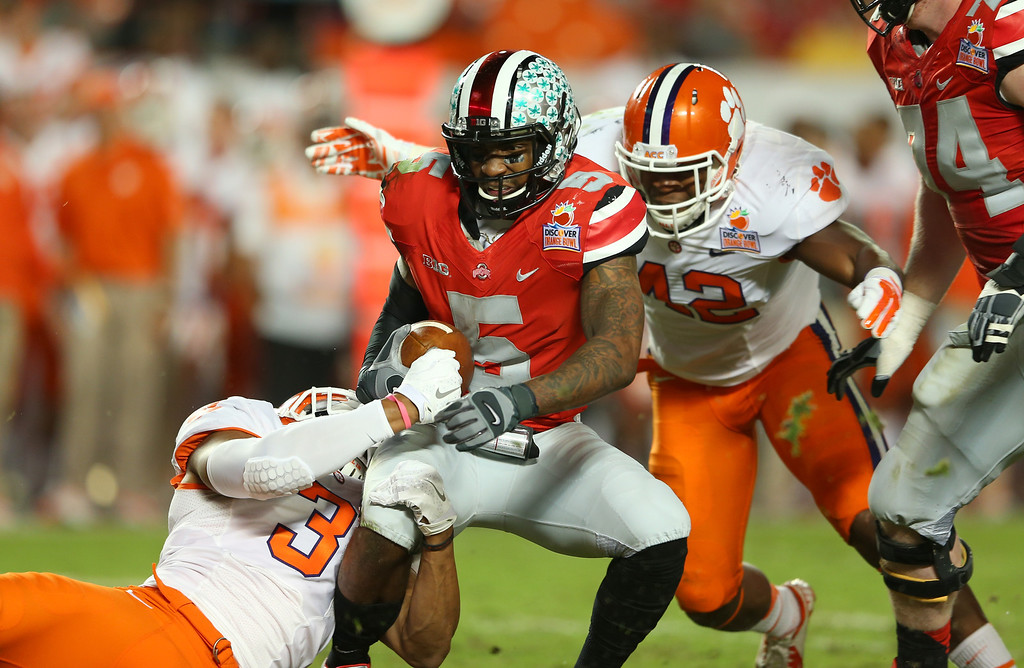 Description of . MIAMI GARDENS, FL - JANUARY 03: Braxton Miller #5 of the Ohio State Buckeyes is sacked in the second quarter by Vic Beasley #3 and Stephone Anthony #42 of the Clemson Tigers during the Discover Orange Bowl at Sun Life Stadium on January 3, 2014 in Miami Gardens, Florida.  (Photo by Mike Ehrmann/Getty Images)