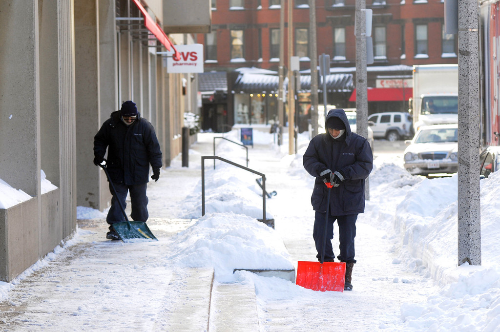 Description of . Workers clear the sidewalk on Edgerly Road after a two day winter storm January 4, 2014 in Boston, Massachusetts. The storm began mid day Thursday with heavy snows overnight into Friday bringing with it extreme cold. (Photo by Darren McCollester/Getty Images)