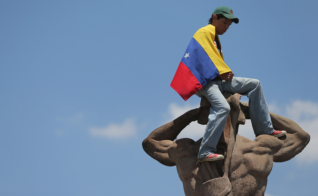 Description of . A young man wears a Venezuelan flag atop a statue outside the funeral for Venezuelan President Hugo Chavez at the Military Academy on March 8, 2013 in Caracas, Venezuela..  (Photo by Mario Tama/Getty Images)