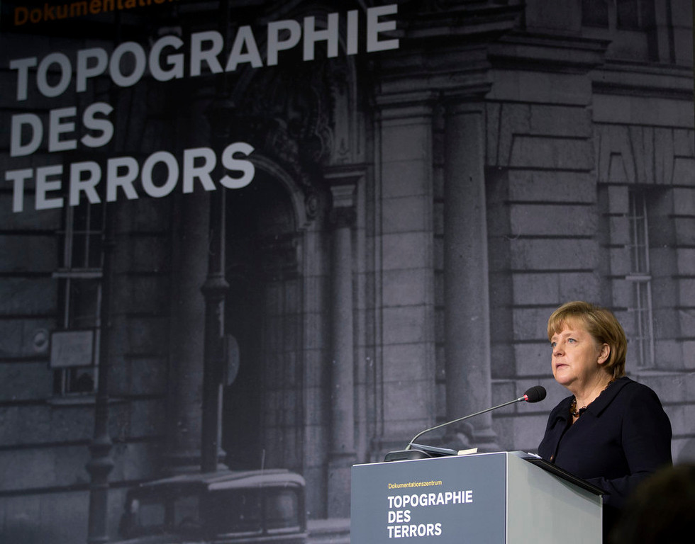 Description of . German Chancellor Angela Merkel speaks as she opens the exhibition 'Berlin 1933 - the way to despotism' at the Topography of Terror museum in Berlin, Germany, Wednesday, Jan. 30, 2013. The Topography of Terror museum is located at the area where the headquarters of the Gestapo and SS were destroyed by allied bombing. (AP Photo/Michael Sohn)