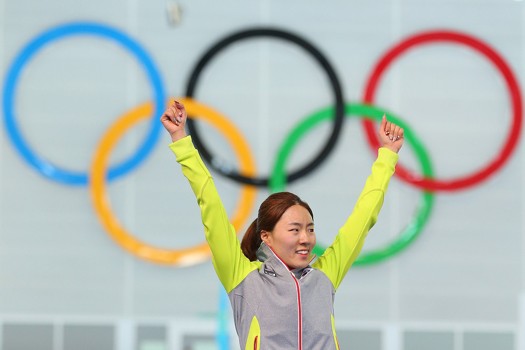 Description of . Gold medalist Sang Hwa Lee of South Korea celebrates on the podium during the flower ceremony for the Speed Skating Women\'s 500m Event during day 4 of the Sochi 2014 Winter Olympics at at Adler Arena Skating Center on February 11, 2014 in Sochi, Russia.  (Photo by Quinn Rooney/Getty Images)