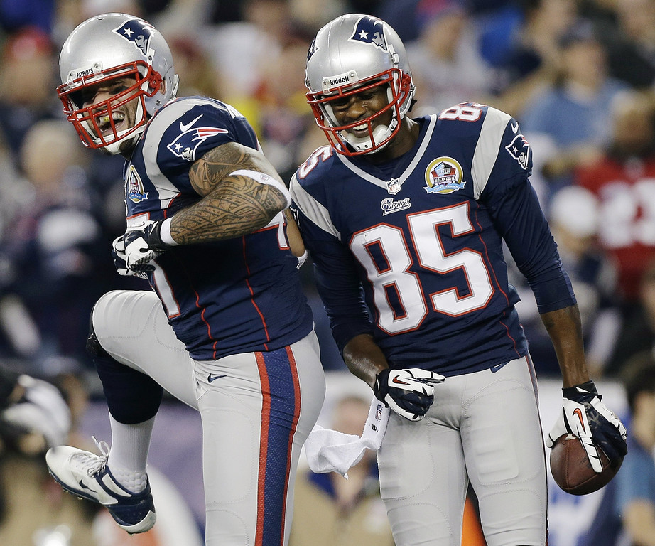 Description of . New England Patriots wide receiver Brandon Lloyd (85) celebrates his touchdown pass with tight end Aaron Hernandez (81) during the first quarter of an NFL football game against the Houston Texans in Foxborough, Mass., Monday, Dec. 10, 2012. (AP Photo/Elise Amendola)