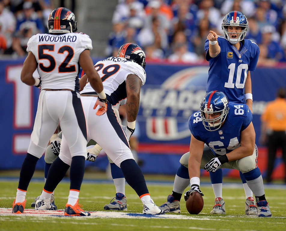 Description of . New York Giants quarterback Eli Manning (10) points out at Denver Broncos outside linebacker Wesley Woodyard (52) during the second quarter September 15, 2013 MetLife Stadium. (Photo by John Leyba/The Denver Post)