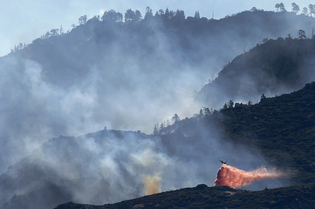 Description of . An air tanker drops fire retardant on a hot spot as firefighters continue to battle a wildfire on Friday, Aug. 9, 2013, near Banning, Calif. (AP Photo/Jae C. Hong)