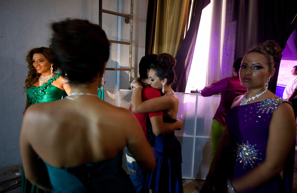 Description of . In this Jan. 26, 2013 photo, beauty contestant Ilce Sahagun, center right, embraces an unidentified person backstage alongside other contestants at the