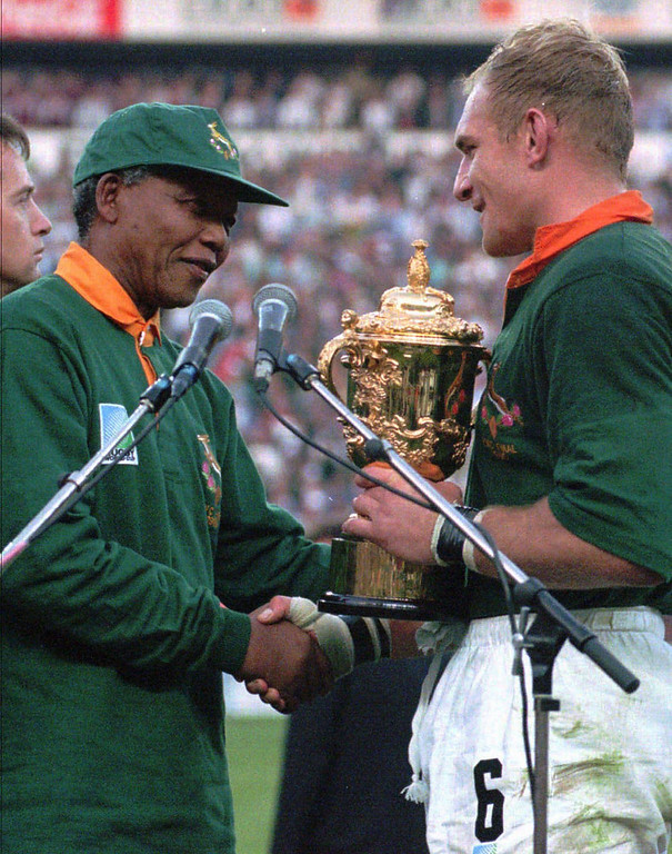 Description of . This June 24, 1995, file photo shows South African rugby captain Francios Pienaar, right, receiving the Rugby World Cup trophy from President Nelson Mandela, left, who wears a South African rugby shirt, after South Africa defeated New Zealand in the finals in Johannesburg. Fifteen years later, another World Cup on South African soil has the power to shape the country anew.  (AP Photo / Ross Setford, File)