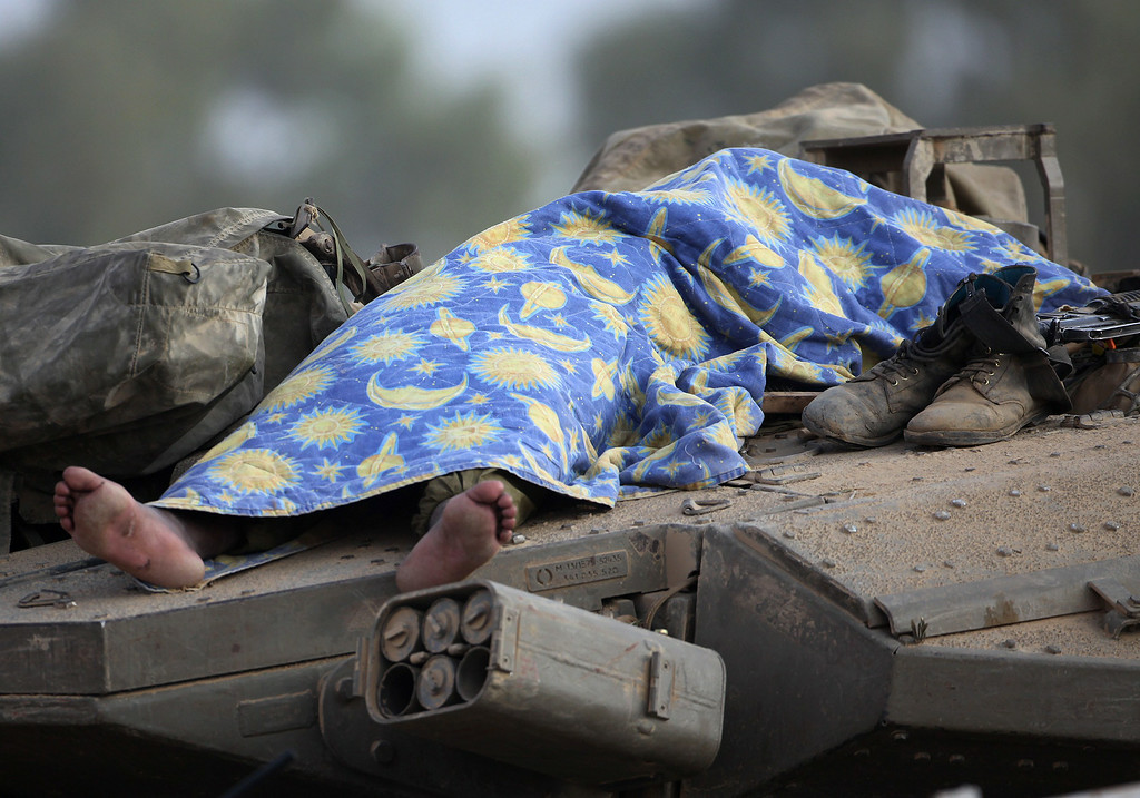 Description of . An Israeli soldier sleeps on a tank positioned along the border between Israel and the Hamas-controlled Gaza Strip on July 29, 2014. Bloodshed in war-torn Gaza surged on with dozens more Palestinians killed as the conflict raged into a fourth week and Iran accused Israel of genocide in the tiny enclave. AFP PHOTO/ DAVID  BUIMOVITCH/AFP/Getty Images