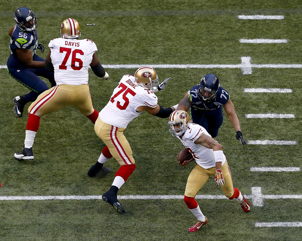 . Quarterback Colin Kaepernick #7 of the San Francisco 49ers carries the ball against the Seattle Seahawks during the 2014 NFC Championship at CenturyLink Field on January 19, 2014 in Seattle, Washington.  (Photo by Tom Pennington/Getty Images)