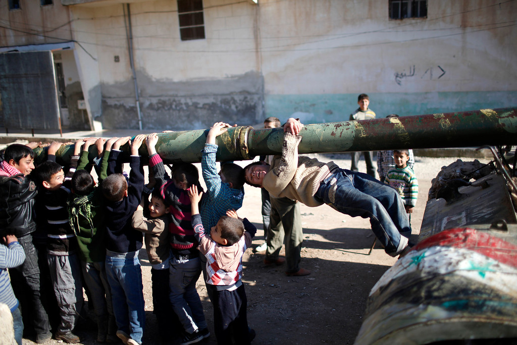 Description of . Children hang from the barrel of a tank, which was captured by the Free Syrian Army, as it is repaired in Azaz city, north Aleppo, December 30,2012.    REUTERS/Ahmed Jadallah