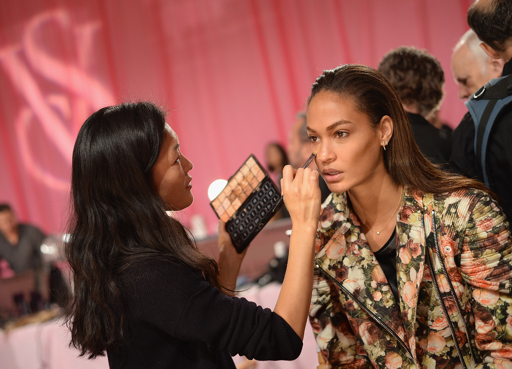 Description of . Model Joan Smalls prepares at the 2013 Victoria's Secret Fashion Show hair and make-up room at Lexington Avenue Armory on November 13, 2013 in New York City.  (Photo by Dimitrios Kambouris/Getty Images for Victoria's Secret)