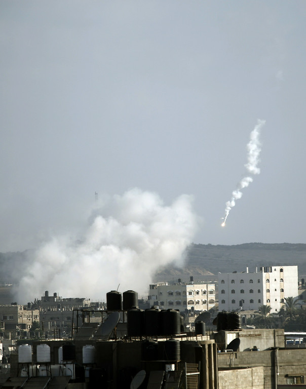 Description of . A picture shows a flare and rising smoke following a missile fired by Israeli aircraft on homes in Beit Lahia, in the northern of Gaza Strip, on July 16, 2014. New Israeli air and tank strikes in Gaza killed several people, medics said, bringing the death toll from Israel's operation in the besieged Palestinian territory to 205. AFP PHOTO/MOHAMMED ABED/AFP/Getty Images