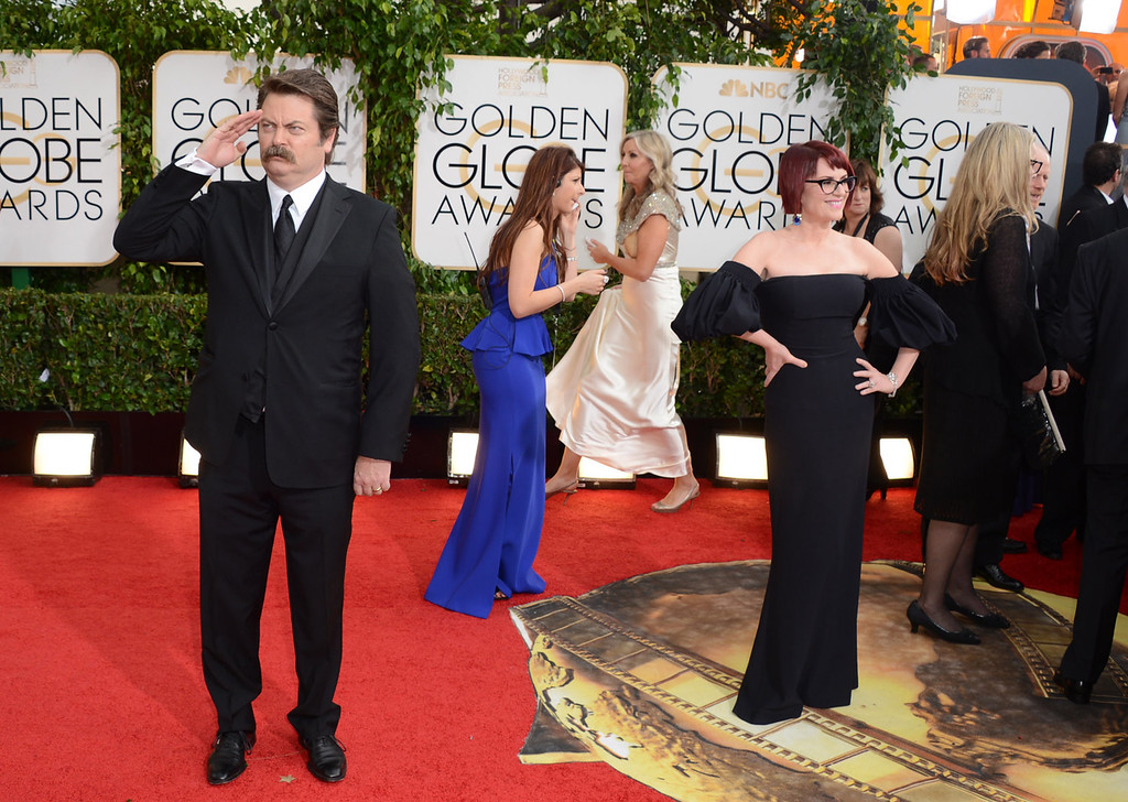 Description of . Nick Offerman, left, salutes the crowd as his wife Megan Mullally poses at the 71st annual Golden Globe Awards at the Beverly Hilton Hotel on Sunday, Jan. 12, 2014, in Beverly Hills, Calif. (Photo by Jordan Strauss/Invision/AP)
