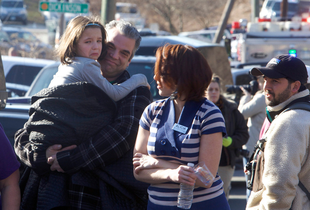 Description of . Parents pick-up children outside Sandy Hook Elementary School after a shooting in Newtown, Connecticut, December 14, 2012.  At least 27 people, including children, were killed on Friday when at least one shooter opened fire at the elementary school in Newtown, Connecticut, CBS News reported, citing unnamed officials. REUTERS/Michelle McLoughlin