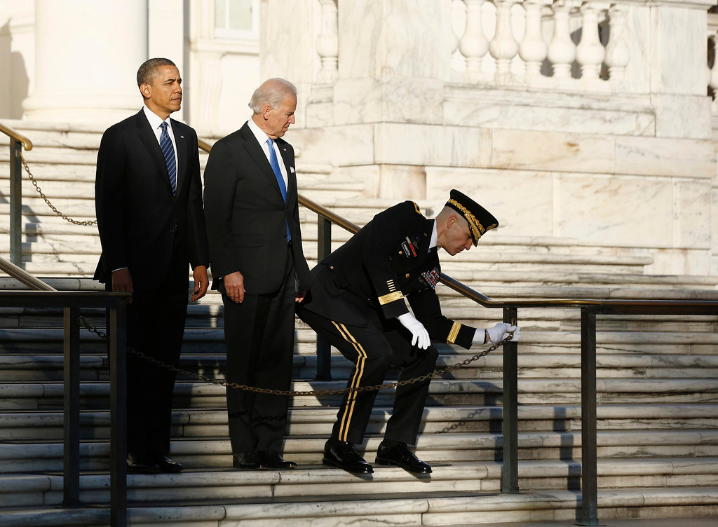 Description of . U.S. President Barack Obama and Vice President Joe Biden wait as U.S. Army Military District of Washington Major General Michael Linnington struggles to unchain a fence before they lay a wreath at the Tomb of the Unknown Soldier at Arlington National Cemetery near Washington, January 20, 2013. Obama will take the official oath of office in a small, private ceremony at the White House on Sunday, setting a more subdued tone for his second inauguration than his historic swearing-in four years ago. Following a wreath-laying ceremony at Arlington National Cemetery, Obama will be sworn in at the White House at 11:55 a.m. EST (1655 GMT).      REUTERS/Jason Reed