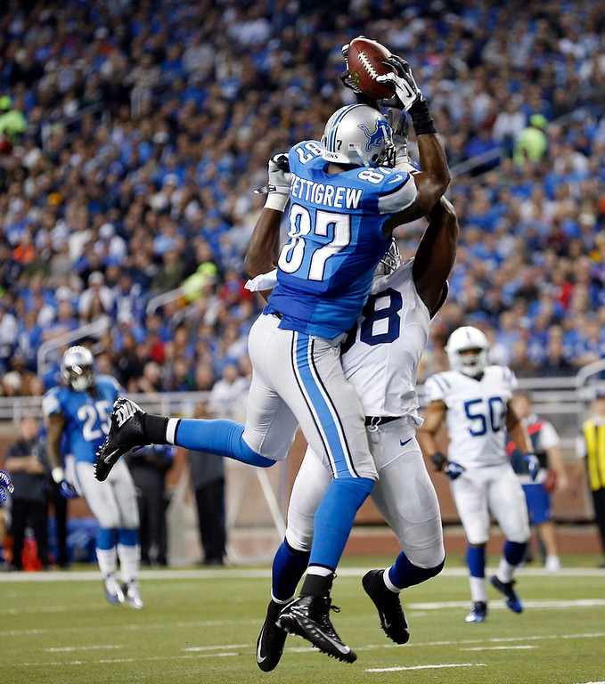 Description of . Detroit Lions tight end Brandon Pettigrew (87), defended by Indianapolis Colts inside linebacker Moise Fokou (58), catches the ball before falling into the end zone after a 16-yard reception for a touchdown during the first quarter of an NFL football game at Ford Field in Detroit, Sunday, Dec. 2, 2012. (AP Photo/Rick Osentoski)