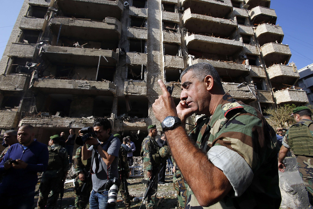 Description of . A Member of the Lebanese army talk on the phone at the site of a blast in Bir Hassan neighborhood in southern Beirut on November 19, 2013. AFP PHOTO/ANWAR  AMRO/AFP/Getty Images