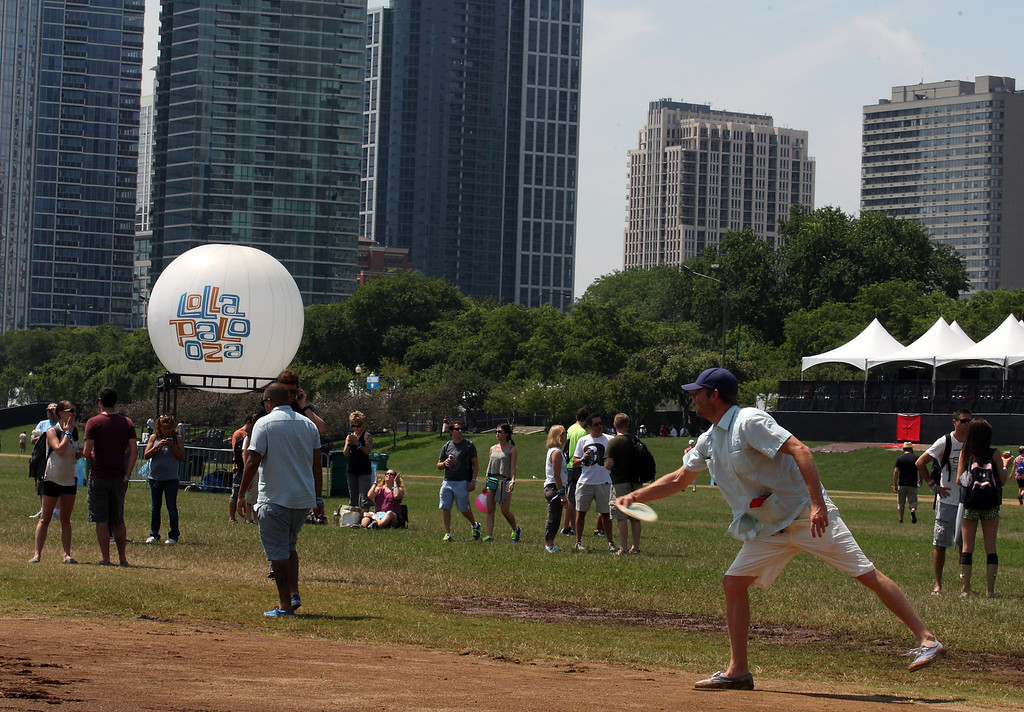Description of . A man throws a frisbee as fans begin entering day 1 of Lollapalooza 2013 at Grant Park on Friday, August 2, 2013 in Chicago. (Photo by Steve Mitchell/Invision/AP)