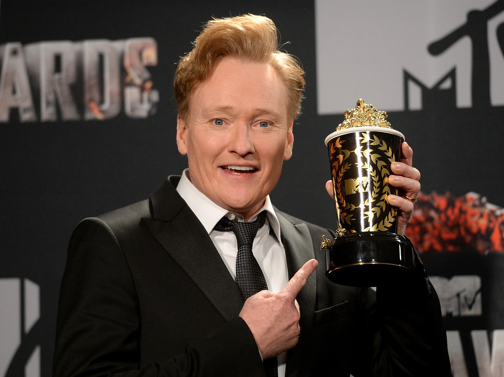 Description of . Host Conan O'Brien (holding the Golden Popcorn Award) poses in the press room during the 2014 MTV Movie Awards at Nokia Theatre L.A. Live on April 13, 2014 in Los Angeles, California.  (Photo by Jason Merritt/Getty Images for MTV)