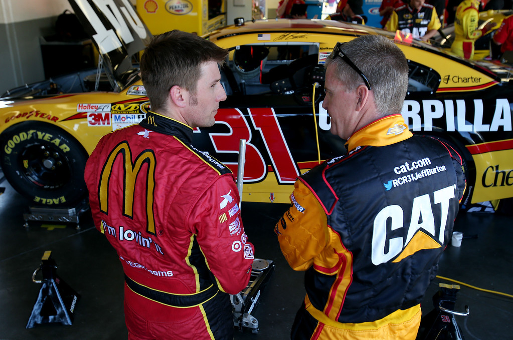 . DAYTONA BEACH, FL - FEBRUARY 20:  Jeff Burton, driver of the #31 Caterpillar Chevrolet, talks to Jamie McMurray, driver of the #1 McDonald\'s Chevrolet, in the garage area during practice for the NASCAR Sprint Cup Series Daytona 500 at Daytona International Speedway on February 20, 2013 in Daytona Beach, Florida.  (Photo by Matthew Stockman/Getty Images)