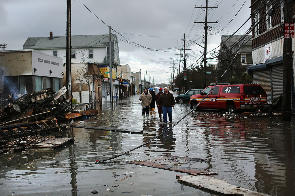 . People look at homes and businesses destroyed during Hurricane Sandy on October 30, 2012 in the Rockaway section of the Queens borough of New York City. At least 40 people were reportedly killed in the U.S. by Sandy as millions of people in the eastern United States have awoken to widespread power outages, flooded homes and downed trees. New York City was hit especially hard with wide spread power outages and significant flooding in parts of the city.  (Photo by Spencer Platt/Getty Images)
