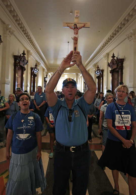 Description of . Michael Benavides of Austin holds up a crucifix and leads a group of pro-life supporters into the Texas State capitol on July 1, 2013 in Austin, Texas. This is the first day of a second legislative special session called by Texas Gov. Rick Perry to pass a restrictive abortion law through the Texas legislature. The first attempt was defeated after opponents of the law were able to stall the vote until after first special session had ended.  (Photo by Erich Schlegel/Getty Images)