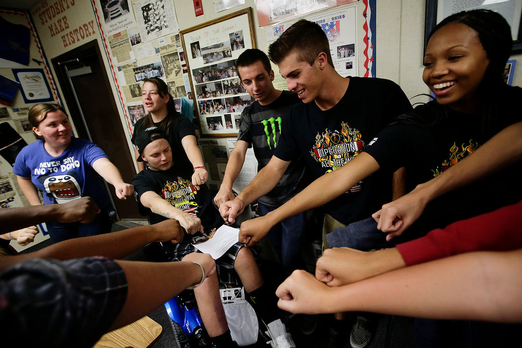 Description of . 27-year-old Iraq war veteran Jerral Hancock, sitting on an electric wheelchair, and members of Operation All The Way Home (OATH) chant their slogans after a meeting at Lancaster High School on Monday, Oct. 21, 2013, in Lancaster, Calif. When the seniors in Jamie Goodreau's high school history class learned Hancock was once stuck in his modest mobile home for months when his handicapped-accessible van broke down, they decided to build him a new house from the ground up.  It would be their end-of-the-year project to honor veterans, something Goodreau's classes have chosen to do every year for the past 15 years. (AP Photo/Jae C. Hong)