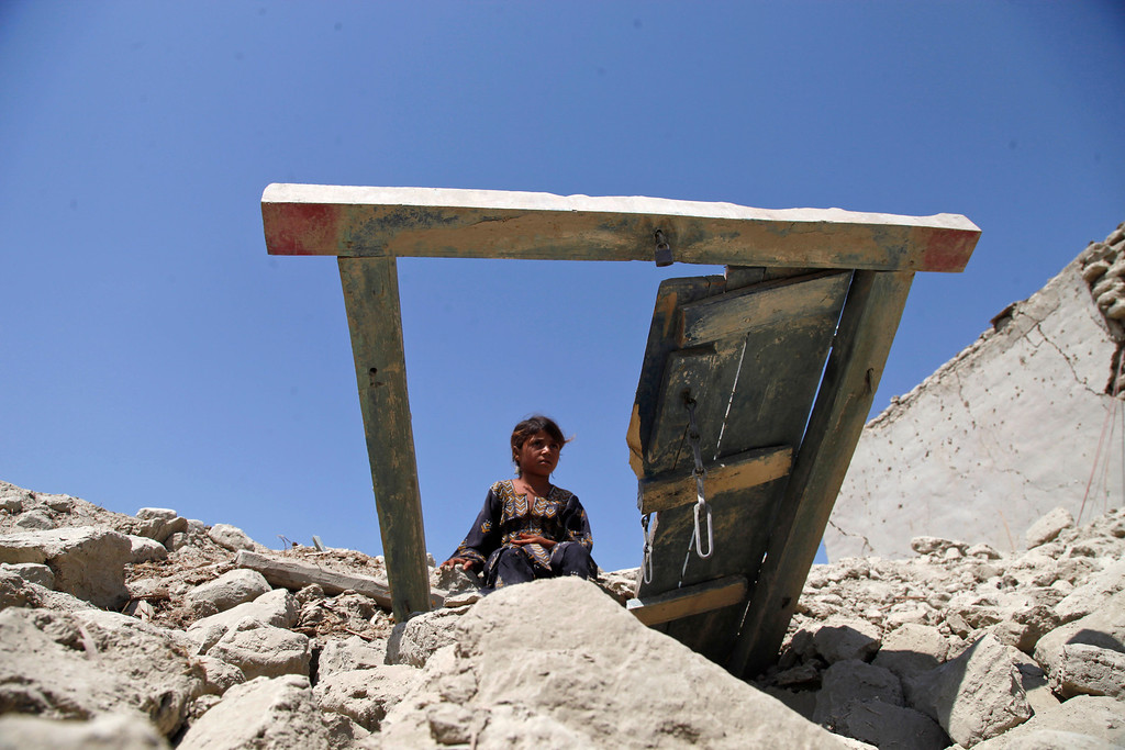 Description of . A Pakistani girl sits on the rubble of her house destroyed by Tuesday's earthquake in Labach, the remote district of Awaran in Baluchistan province, Pakistan, Thursday, Sept. 26, 2013.  (AP Photo/Shakil Adil)
