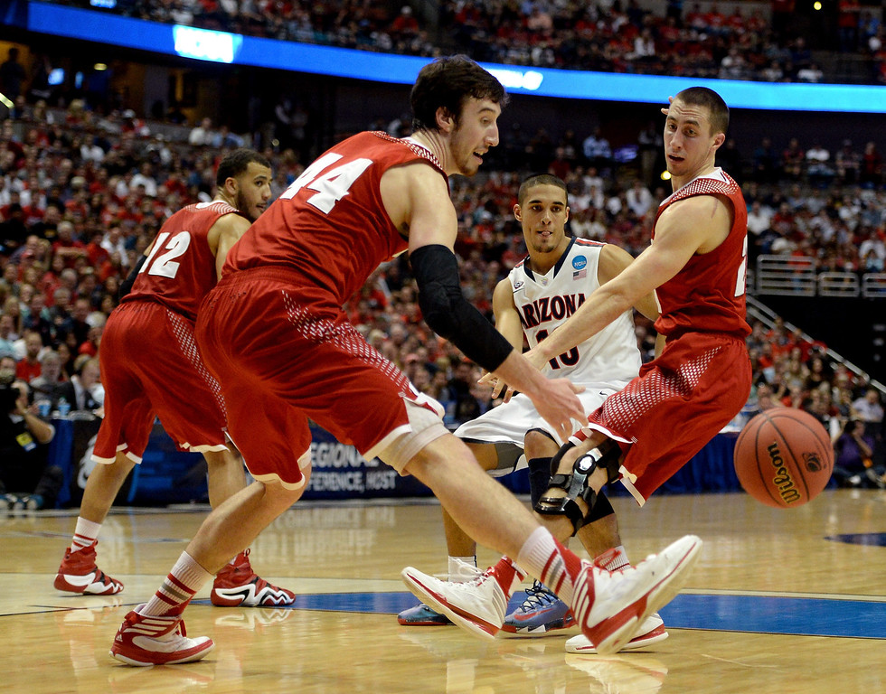 Description of . Nick Johnson #13 of the Arizona Wildcats passes the ball between Frank Kaminsky #44 and Josh Gasser #21 of the Wisconsin Badgers in the first half during the West Regional Final of the 2014 NCAA Men's Basketball Tournament at the Honda Center on March 29, 2014 in Anaheim, California.  (Photo by Harry How/Getty Images)