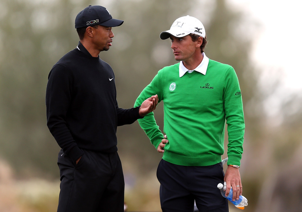 Description of . MARANA, AZ - FEBRUARY 21:  (L-R) Tiger Woods and Charles Howell III talk on the 11th hole tee box during the first round of the World Golf Championships - Accenture Match Play at the Golf Club at Dove Mountain on February 21, 2013 in Marana, Arizona. Round one play was suspended on February 20 due to inclimate weather and is scheduled to be continued today.  (Photo by Jed Jacobsohn/Getty Images)