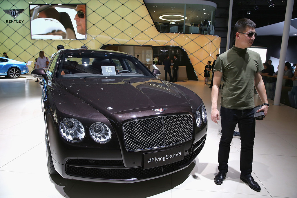 Description of . A potential consumer stands beside a Bentley Flying Spur V8 car during the 2014 Beijing International Automotive Exhibition at China International Exhibition Center on April 21, 2014 in Beijing, China.   (Photo by Feng Li/Getty Images)