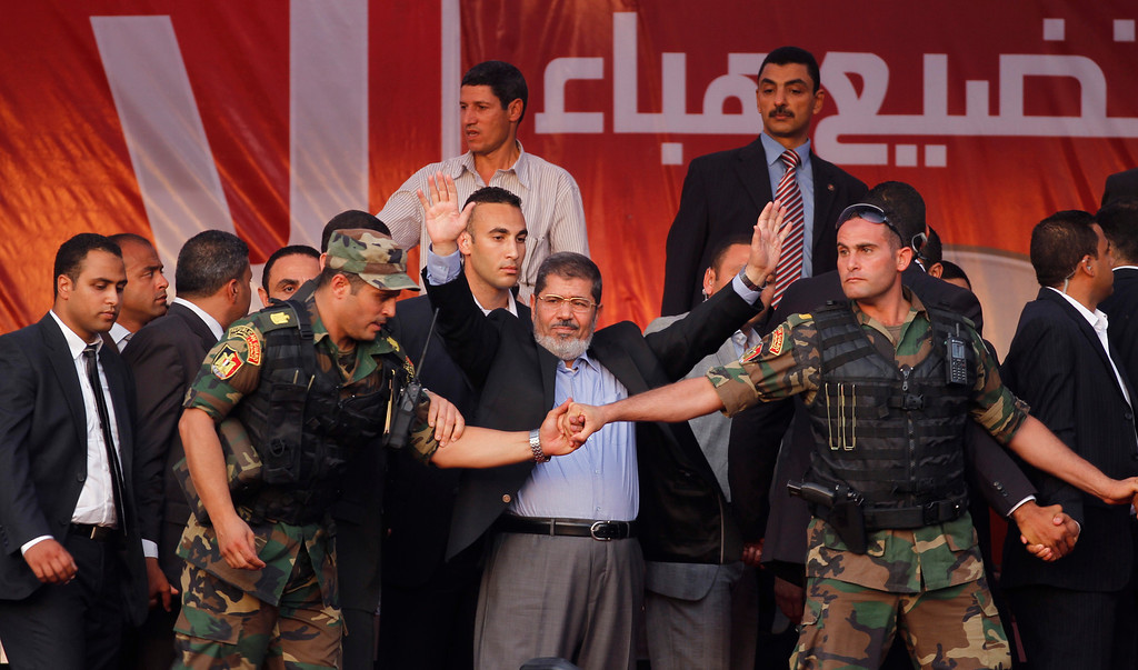 Description of . In this June 29, 2012 file photo, Egypt's President-elect Mohammed Morsi waves to supporters after giving a speech at Tahrir Square in Cairo.  (AP Photo/Khalil Hamra, File)