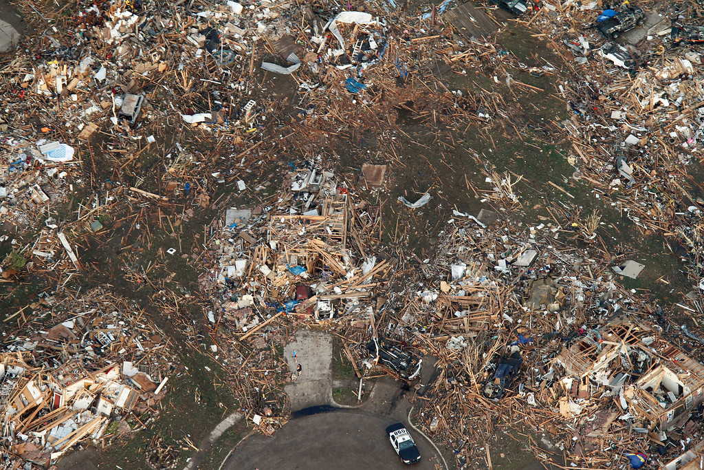 Description of . This aerial photo shows the remains of homes hit by a massive tornado in Moore, Okla., Monday May 20, 2013. A tornado roared through the Oklahoma City suburbs Monday, flattening entire neighborhoods, setting buildings on fire and landing a direct blow on an elementary school. (AP Photo/Steve Gooch)