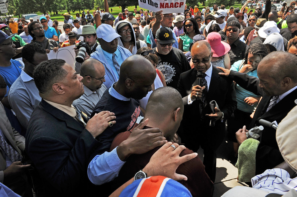 Description of . Reverands and members of the African American community of Denver pray together  during the rally in City Park in Denver, CO on July 14, 2013.  Several hundred people turned out  to show their disappointment in the acquittal of George Zimmerman in the murder trail of Trayvon Martin.  Zimmerman is the Florida man who shot and killed Trayvon Martin.