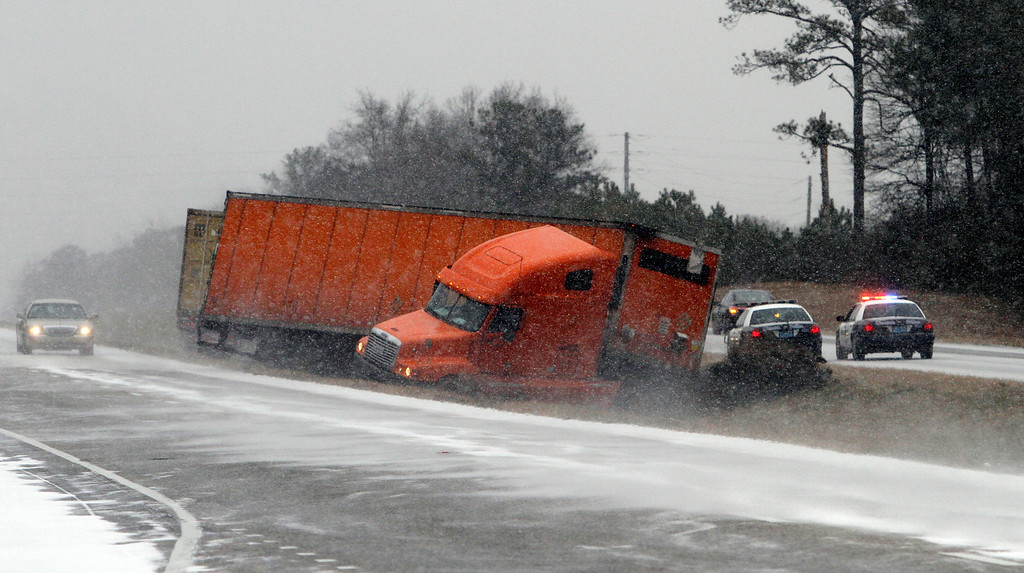Description of . A truck slides into the median while trying to avoid another wrecked truck in the snow  on I-65 several road   Tuesday, Jan. 28, 2014, in Clanton, Ala.  A rare storm left a slippery layer of ice and snow across a region unaccustomed to dealing with the wintry threat.   (AP Photo/Butch Dill)