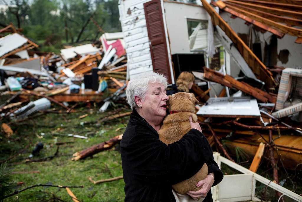 Description of . Constance Lambert embraces her dog after finding it alive when returning to her destroyed home in Tupelo, Miss., Monday, April 28, 2014. Lambert was at an event away from her home when the tornado struck and rushed back to check on her pets. (AP Photo/The Commercial Appeal, Brad Vest)