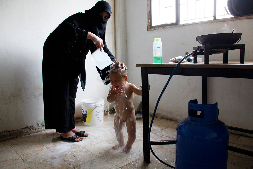 Description of . A Syrian refugee woman gives her child a shower in the kitchen of an abandoned school in Wadi Khaled area, northern Lebanon September 28, 2011. More than 3,800 displaced Syrian refugees have registered with the United Nations refugee agency (UNHCR) in north Lebanon, which borders Syria's Homs province, a particularly bloody centre of the uprising against President Bashar al-Assad. REUTERS/Mohamed Azakir