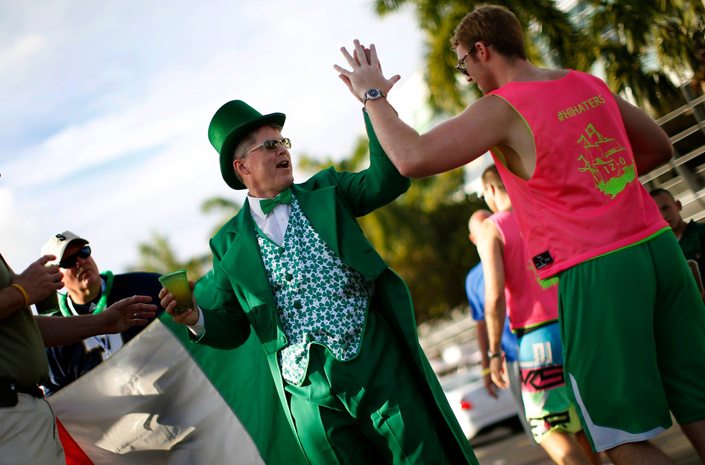 Description of . A Notre Dame Fighting Irish fan dressed as a leprechaun high-fives another fan outside Sun Life stadium before the BCS National Championship college football game between the Alabama Crimson Tide and the Notre Dame Fighting Irish in Miami, Florida January 7, 2013. REUTERS/Mike Segar