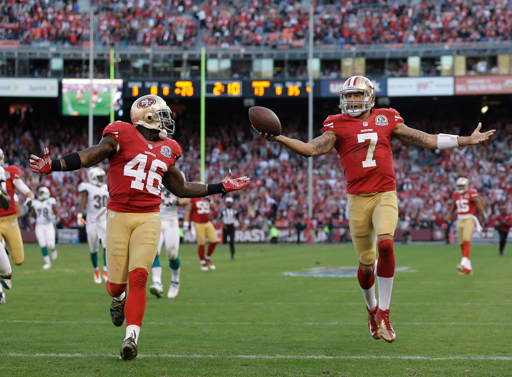 Description of . San Francisco 49ers quarterback Colin Kaepernick, right, celebrates after scoring a touchdown on a 50-yard run as San Francisco 49ers tight end Delanie Walker, left, looks on during the fourth quarter of an NFL football game in San Francisco, Sunday, Dec. 9, 2012. San Francisco won the game 27-13. (AP Photo/Marcio Jose Sanchez)