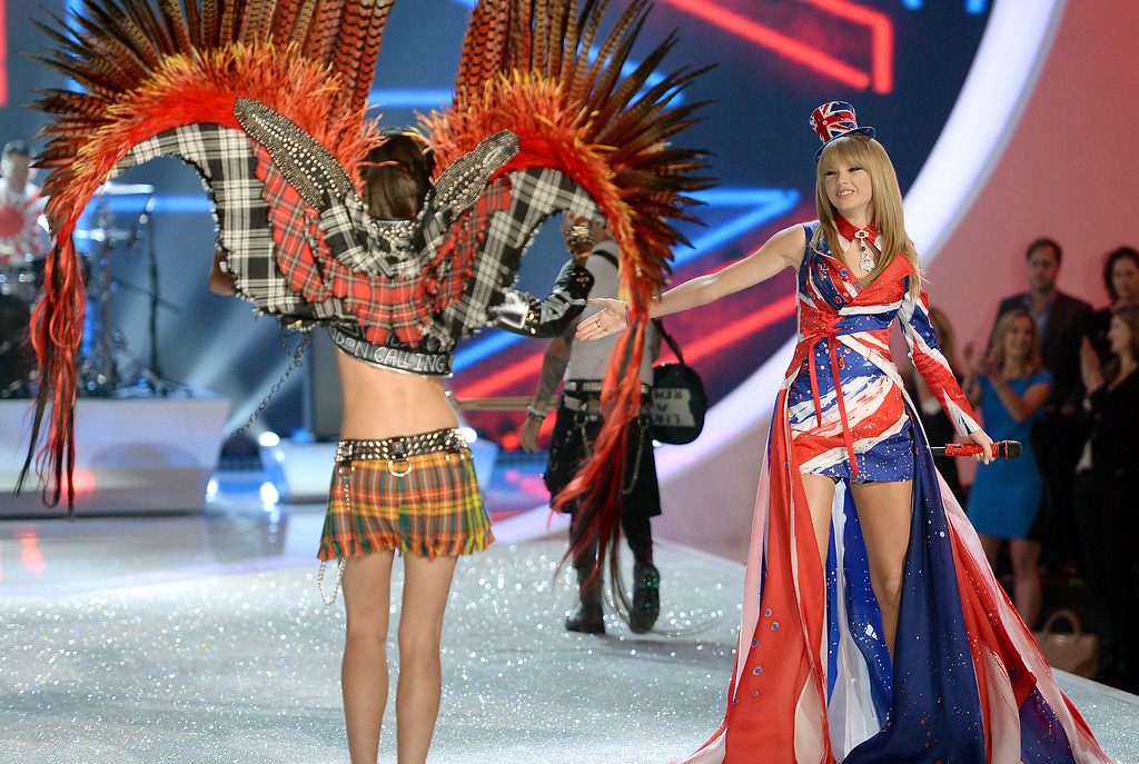 Description of . Singer Taylor Swift (R) performs and model Lily Aldridge walks the runway at the 2013 Victoria's Secret Fashion Show at Lexington Avenue Armory on November 13, 2013 in New York City.  (Photo by Dimitrios Kambouris/Getty Images for Victoria's Secret)