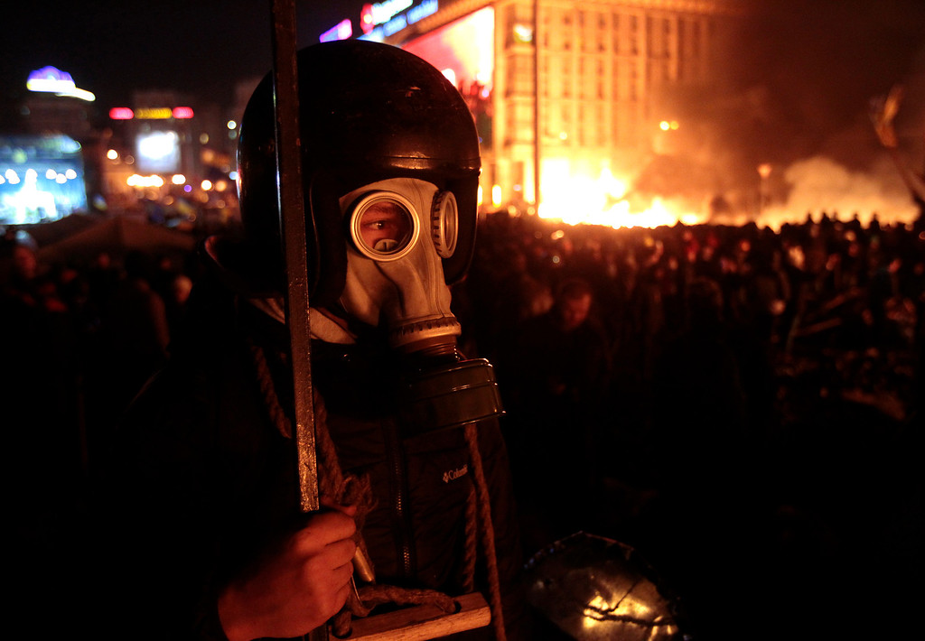 Description of . Anti-government protesters clash with riot police in Kiev's Independence Square, the epicenter of the country's current unrest, Kiev, Ukraine, Tuesday, Feb. 18, 2014.  (AP Photo/Sergei Chuzavkov)