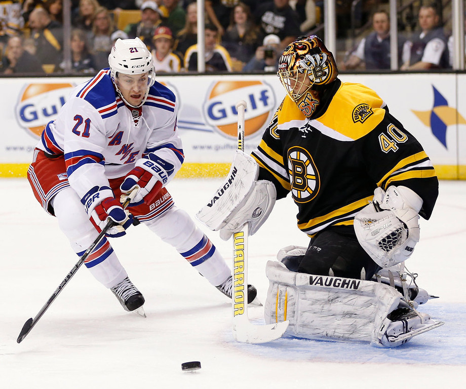 Description of . New York Rangers' Derek Stepan (21) skates for the rebound off Boston Bruins goalie Tuukka Rask (40), of Finland, during the first period of an NHL hockey game in Boston, Saturday, Jan. 19, 2013. (AP Photo/Michael Dwyer)