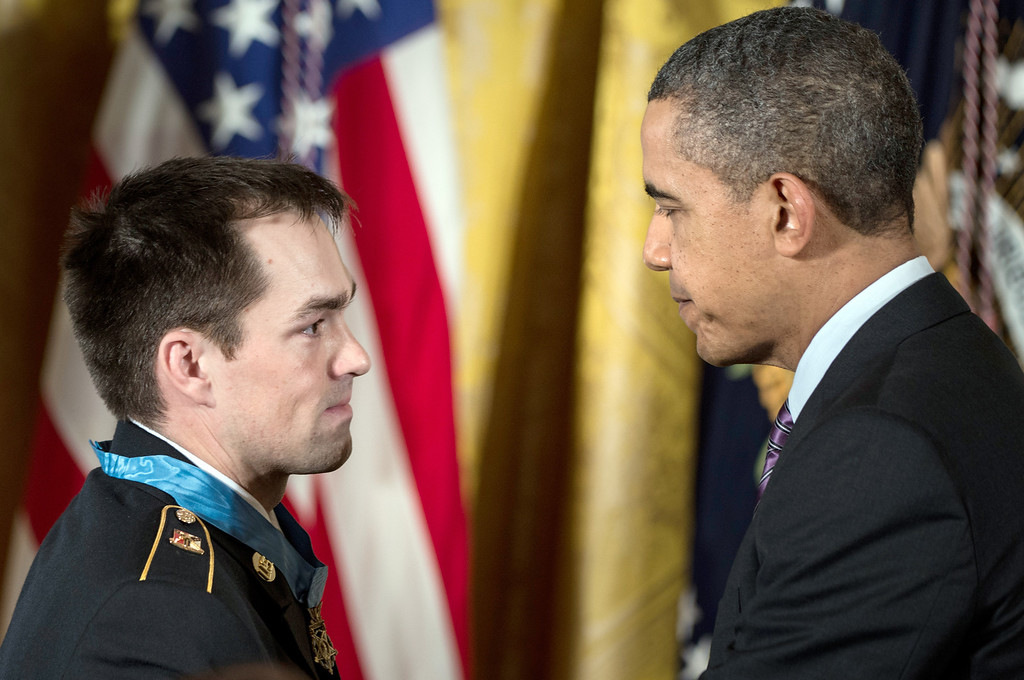 Description of . US President Barack Obama thanks US Army Staff Sargent Clinton Romesha during a Medal of Honor ceremony in the East Room of the White House February 11, 2013 in Washington, DC. AFP PHOTO/Brendan  SMIALOWSKI/AFP/Getty Images