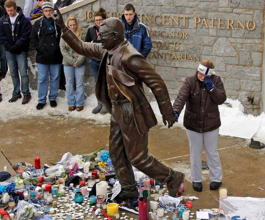 Description of . In this Jan. 22, 2012 file photo, a woman pays her respects at a statue of Joe Paterno outside Beaver Stadium on the Penn State University campus after learning of his death in State College, Pa. (AP Photo/Gene J. Puskar, File)