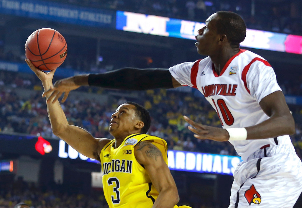 Description of . Michigan Wolverines guard Trey Burke (L) shoots while being guarded by Louisville Cardinals center Gorgui Dieng during the first half of their NCAA men\'s Final Four championship basketball game in Atlanta, Georgia April 8, 2013. REUTERS/Chris Keane